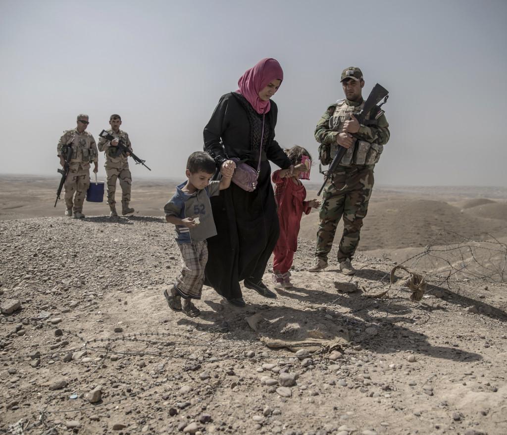 Fronten mot IS. I bergen utanför Mosul har kurdiska styrkorna, Persmerga, sin frontlinje mot IS. 12 män, kvinnor och barn som lyckats fly från en IS-kontrollerad by, de har tagit sig genom öknen och sökt skydd hos de kurdiska styrkorna. De förhörs och kontrolleras noga innan de förs vidare på ett lasbilsflak mot ytterligare förhör och senare till flyktingläger. Foto: Magnus Wennman